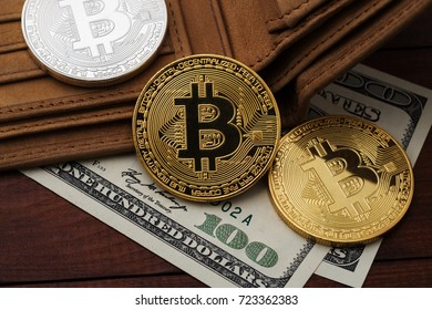 Metal bitcoins and hundred dollar bills in brown leather wallet.