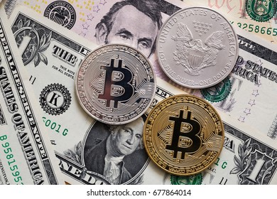 metal bitcoins and silver  dollar on bills background