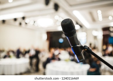 Metal black microphone in holder stand on background of light hall room with occasion celebrated