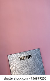 "Metal board with ""note"" written on it, against pink wall background."
