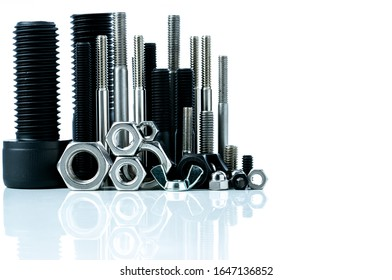 Metal bolts and nuts on white background. Fasteners equipment. Hardware tools. Stud bolt, hex nuts, and hex head bolts in workshop. Threaded fastener use in automotive engineering. Hexagonal bolt. - Shutterstock ID 1647136852