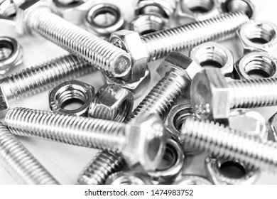Metal bolts and nuts  in a row background. Chromed screw bolts and nuts isolated. Steel bolts and nuts pattern. Set of Nuts and bolts. Tools for work. Black and white