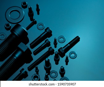 Metal Bolts, nuts, and washers. Fasteners equipment. Hardware tools. Stud bolt, flat washers, hex nuts, and hex head bolts in workshop. Threaded fastener use in automotive engineering. Hexagonal bolt. - Shutterstock ID 1590735907