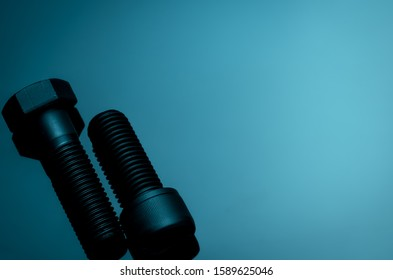 Metal bolts on blue background. Hardware tools. Closeup hex head bolt and socket cap bolt with copy space. Threaded fastener use in automotive engineering. Hexagonal bolt. High strength fasten bolt.