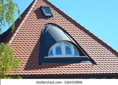 Metal Bow Dormer Window and Roof Window on the Tiled Roof of a modernized Residential Building