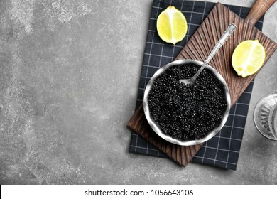 Metal bowl with black caviar on grey background