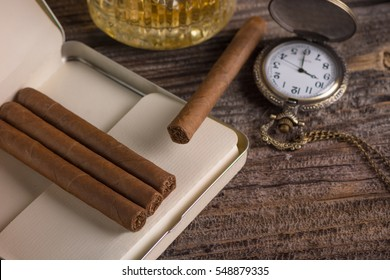 Metal box of cigars and glass of whiskey on wooden background