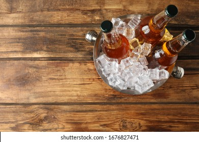 Metal bucket with beer and ice cubes on wooden background, top view. Space for text