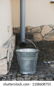 Metal bucket with handle standing by a rain pipe