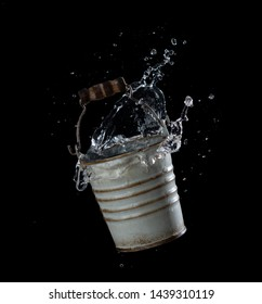 Metal bucket with water splash or explosion flying in the air isolated on black background,Motion blur