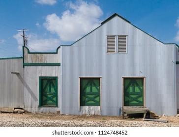 a metal building with 3 green doors