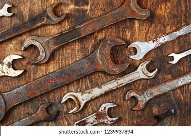 Metal bunch wrench rusty iron metal tools lying on dark wooden table