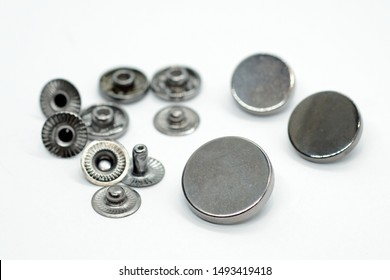 Metal button for clothes, nickel color. Sewing accessories for outerwear production. Components of the press-stud with a flat top on a white background close-up.