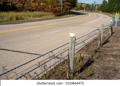 Metal cable guardrails on the side of a cury road, preventing accidents and cars from going into the ditch