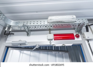 Metal cable tray and alarm system lamp over the door