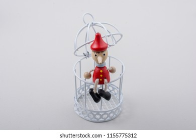 Metal cage and Little puppet pinocchio made of wood