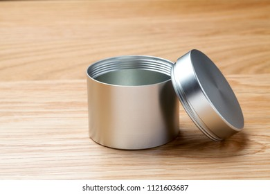 Metal can for tea packaging on wooden table