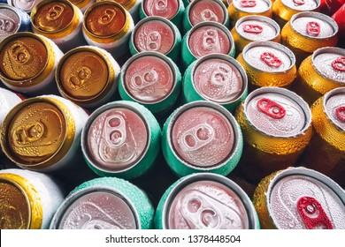 Metal cans of beer with ice cubes in mini refrigerator, close up. Lots of aluminum cans in the ice in the open fridge. Drops of water on a cold can of drink.