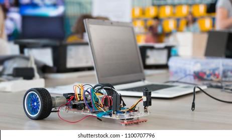 Ein Roboter aus Metall und ein elektronisches Board, das programmiert werden kann. Robotik und Elektronik. Laboratorium. Mathematik, Ingenieurwesen, Naturwissenschaften, Technologie, Computercode. STEM-Ausbildung.