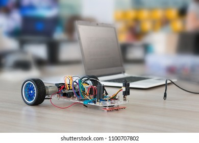 A metal car robot and an electronic board that can be programmed. Robotics and electronics. Laboratory. Mathematics, engineering, science, technology, computer code. STEM education.