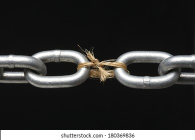 Metal chain with link missing replaced by rope on black background