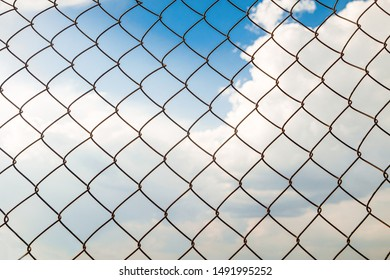 Metal chain links wire-mesh rabitz on a blue cloudy sky background