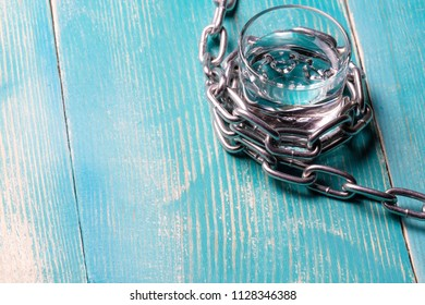 The metal chain is wound on a glass with a transparent liquor, on a wooden painted table