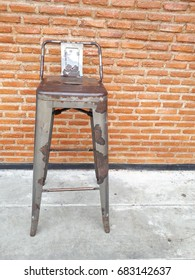 Metal chair stand up front red brick wall