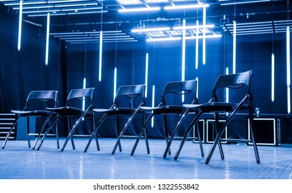 Metal chairs aligned for meeting in  modern business space illuminated with neon lights