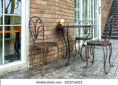 Metal chairs and table, iron chairs and table in front of the door.