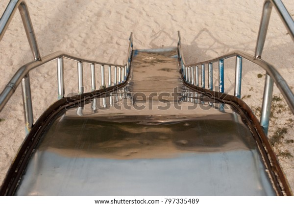 Metal children's slide view from top to bottom, railing handrails, against the background of sand, children's games, playground, summer sun holidays