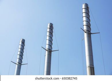 Metal chimneys with antivortic spiral and blue sky in the background .