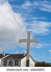 Metal christian cross and blue sky with white clouds.