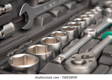 Metal or chrome wrenches and other tools in a suitcase close-up