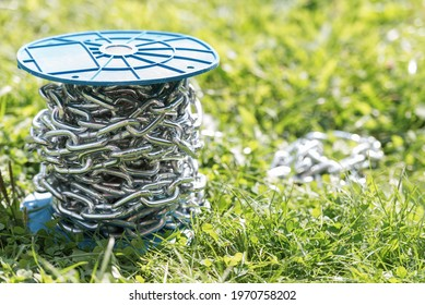 Metal chromed chain. The bay of the shining chain lies in the grass. Under the bright sun lies a coil of chain.