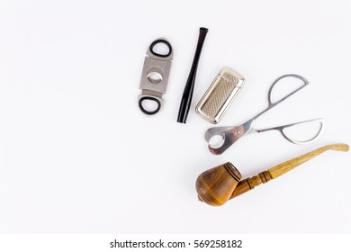 Metal cigar cutters, lighter, cigarette-holder and  wooden pipe isolated on white background