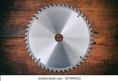 Metal circular saw blade on a wooden background, top view