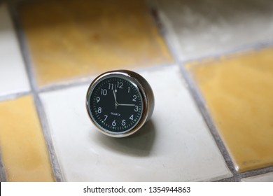 metal clock on ceramic floor