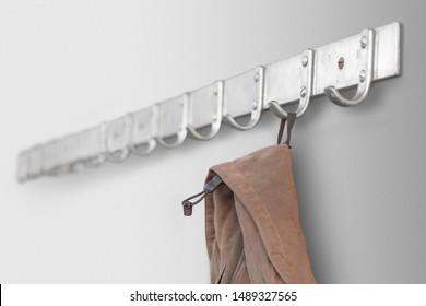 Metal coat hanger with brown coat or jacket on gray wall