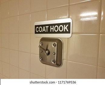 metal coat hook on white tile bathroom wall with sign