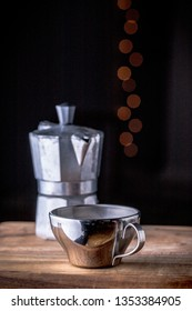 Metal coffee cup and cafetiere on a kitchen counter with dark background