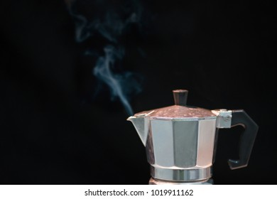 Metal coffee percolator with stream on black background