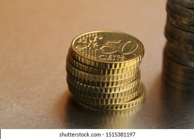 metal coins of 50 cents EU are stacked on a yellow background, financial concept, close-up, copy space