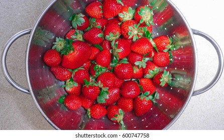 A metal colander with fresh strawberries, being washed. Selective focus.