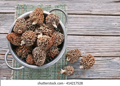 Metal colander with morel on wooden table
