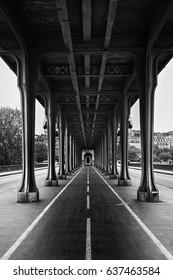 Metal columns and abutments of '' Bir Hakeim '' bridge. People walks and make jogging under the bridge in Paris.The bridge is one of the most famous and historic landmark