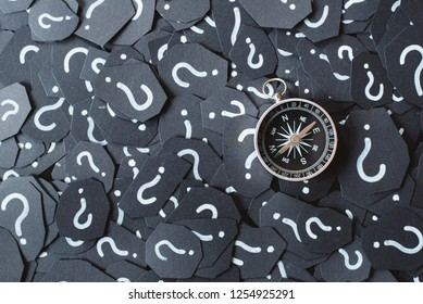 Metal compass on question mark background. Concept of travel, navigation, explore and where to go