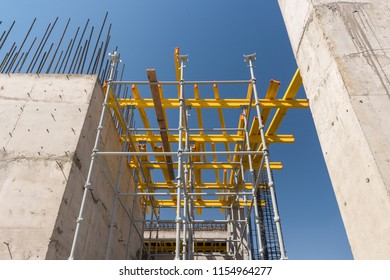 metal concrete structures of the building under construction. scaffolding and supports on a sky background. bottom view