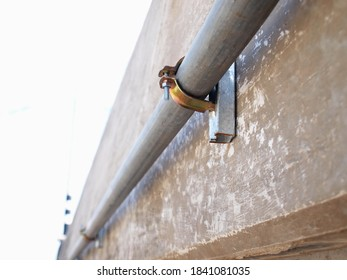 Metal conduit clamp on cement wall. IMC (Intermediate Metal Conduit) pipe locking technology attached to the wall beside the outdoor bridge. Close focus and choose a subject