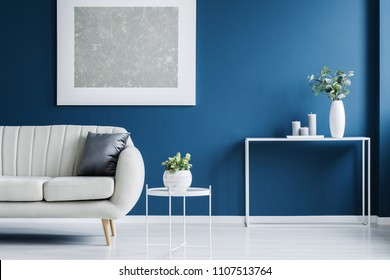 Metal console table with plant in vase and candles standing against blue wall in living room interior with light grey sofa and modern poster
